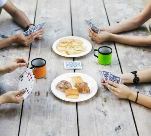 Close up of four people sitting at a table, playing cards.